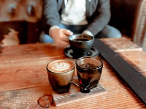 coffee cups on wooden table, someone sitting across table from viewer holding mug, on a date, not ready to date, dating after vaccination